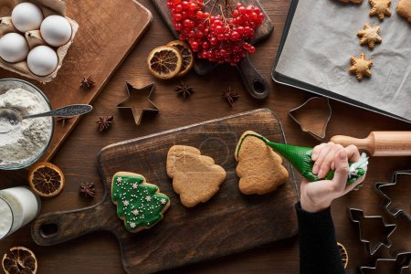 cropped view of woman glazing Christmas cookies on wooden table