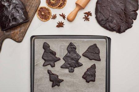 Foto de Vista superior de la masa cruda para galletas de Navidad cerca de bandeja de horno en fondo blanco. - Imagen libre de derechos