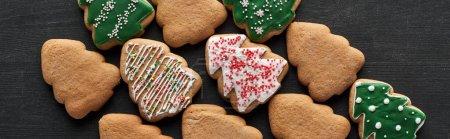 Photo pour Plat étendu avec délicieux biscuits de sapin de Noël glacés sur fond noir, vue panoramique - image libre de droit