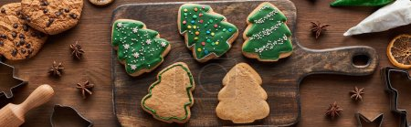 Photo for Top view of glazed Christmas cookies with pastry bag on wooden cutting board, panoramic shot - Royalty Free Image
