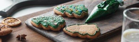 Photo pour Foyer sélectif de biscuits de Noël cuits près du sac à pâtisserie sur une table en bois, vue panoramique - image libre de droit