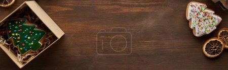 Photo pour Top view of Christmas tree cookies, gift box on wooden table, panoramic shot - image libre de droit