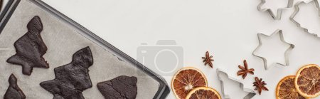 Photo pour Top view of raw Christmas tree cookies on oven tray near winter spices and begh molds, panoramic shot - image libre de droit