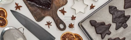 Photo for Top view of raw Christmas tree cookies on oven tray near winter spices, knife and dough molds, panoramic shot - Royalty Free Image