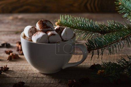 Photo pour Cacao de Noël avec guimauve sur table en bois près d'une branche de pin - image libre de droit