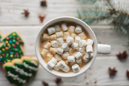 Photo pour Selective focus of Christmas cacao with marshmallow in mug on white wooden table with fir branch and cookies - image libre de droit