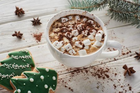 Photo pour Cacao with marshmallow in mug on white wooden table with fir branch and Christmas cookies - image libre de droit