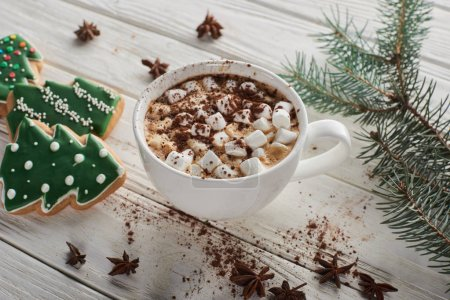 Photo pour Cacao with marshmallow in cup on white wooden table with fir branch and Christmas cookies - image libre de droit
