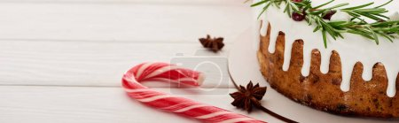 Photo for Christmas pie with icing on white wooden table with candy canes and anise star seeds - Royalty Free Image