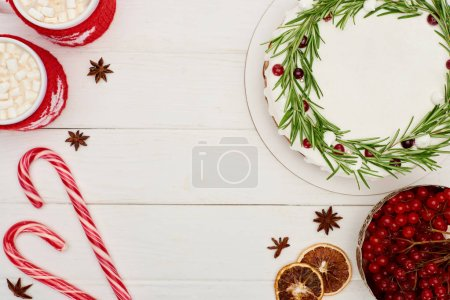 Photo for Top view of christmas pie, viburnum berries, candy canes and two cups of cocoa with marshmallows on white wooden table - Royalty Free Image