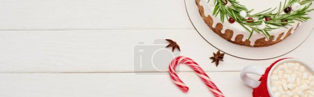 Photo for Top view of christmas pie on white wooden table with candy cane and cup of cocoa with marshmallows - Royalty Free Image