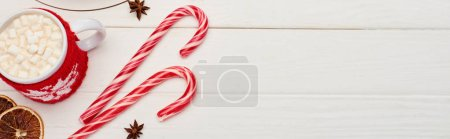 Photo for Top view of christmas candy canes and cup of cocoa with marshmallows on white wooden table - Royalty Free Image