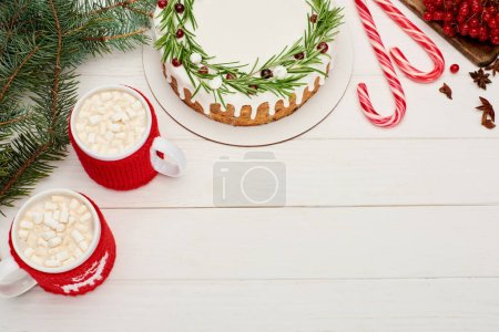 Photo for Top view of two cups of cocoa with marshmallows and christmas pie with icing on white wooden table - Royalty Free Image