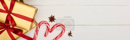 Photo pour Top view of Christmas gift boxes and candy canes on white wooden table - image libre de droit