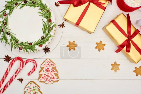top view of christmas pie, cookies and presents on white wooden table