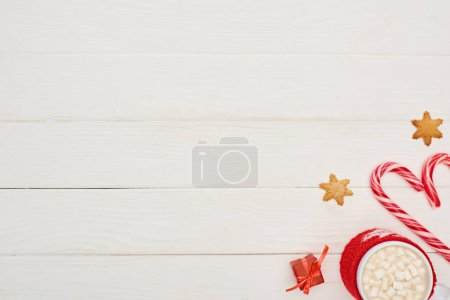 Photo for Top view of christmas candy canes, little gift, cookies and cup of cocoa with marshmallows on white wooden table - Royalty Free Image