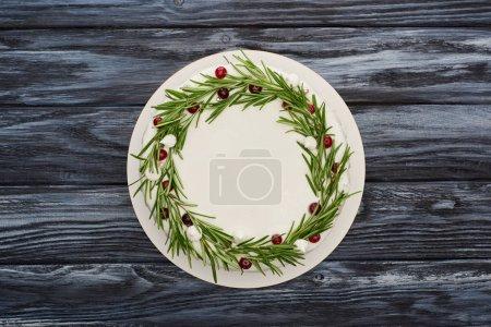 Blick auf traditionelle Weihnachtskuchen mit weißem Zuckerguss, Rosmarin und Preiselbeeren auf dunklem Holztisch