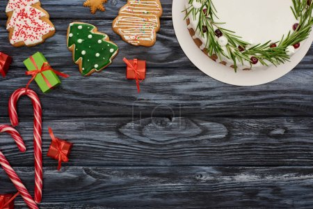 top view of christmas pie, candy canes, little gifts and cookies on dark wooden table