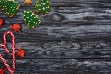Photo for Top view of little gifts, candy canes and christmas tree cookies on dark wooden table - Royalty Free Image