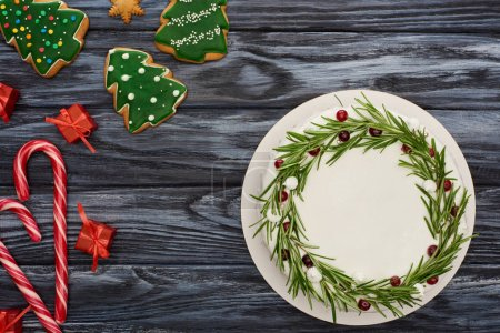 top view of christmas pie with decorations, candy canes, little gifts and cookies on dark wooden table