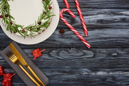 Photo for Top view of christmas pie with rosemary and cranberries, candy canes, fork and knife on napkin on dark wooden table - Royalty Free Image