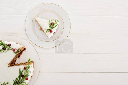 Photo for Top view of christmas pie with icing, rosemary and cranberries on white wooden table - Royalty Free Image