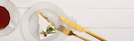 Photo for Top view of piece of christmas pie, tea, fork and knife on white wooden table - Royalty Free Image