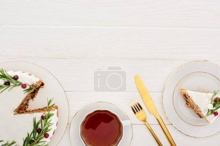 Photo pour Top vue de la tarte de Noël avec romarin et tasse de thé sur table blanche en bois - image libre de droit