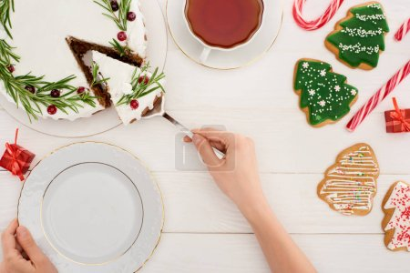 Photo for Cropped view of woman with christmas pie, cup of tea and cookies on white wooden table - Royalty Free Image