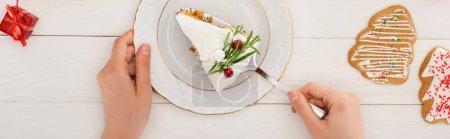 Photo pour Vue recadrée de la femme avec morceau de tarte de Noël et biscuits sur table en bois blanc - image libre de droit