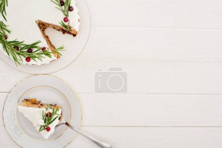 Photo for Top view of sweet christmas pie with rosemary and cranberries on white wooden table - Royalty Free Image