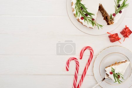 Photo for Top view of christmas pie with rosemary and cranberries on white wooden table with candy canes and little gifts - Royalty Free Image