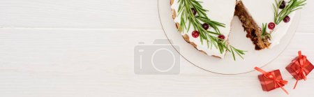 Photo for Top view of christmas pie with rosemary and red berries on white wooden table with little gifts - Royalty Free Image