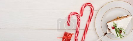 Photo for Top view of piece of christmas pie with rosemary and cranberries on white wooden table with candy canes and little gift - Royalty Free Image