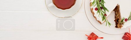 Photo for Top view of christmas pie with rosemary and cranberries on white wooden table with cup of tea little gifts - Royalty Free Image