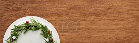 Photo for Top view of christmas pie with white icing, rosemary and cranberries on wooden table - Royalty Free Image