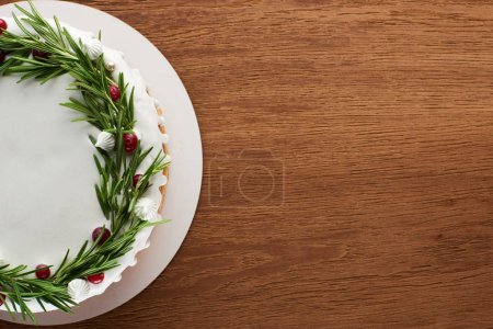 Photo for Top view of traditional christmas pie with icing, rosemary and cranberries on wooden table - Royalty Free Image