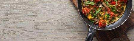 Blick von oben auf leckeres Omelett in der Pfanne auf Holzbrett