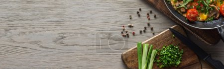 Photo for Top view of  omelet in frying pan with ingredients on wooden table - Royalty Free Image