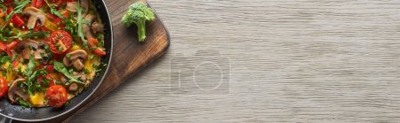 top view of omelet in frying pan on wooden board with fresh broccoli
