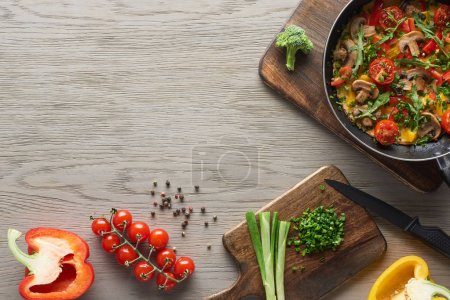 Photo for Top view of delicious homemade omelet in frying pan with cherry tomatoes and ingredients on table - Royalty Free Image