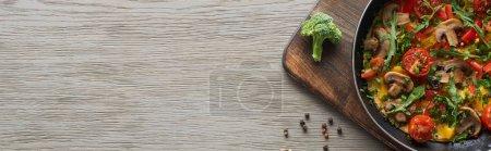 hausgemachtes Omelett mit Gemüse und Gemüse in der Pfanne auf Holzbrett mit frischem Brokkoli