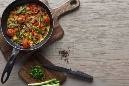 Photo for Top view of omelet in frying pan with ingredients and knife on wooden table - Royalty Free Image