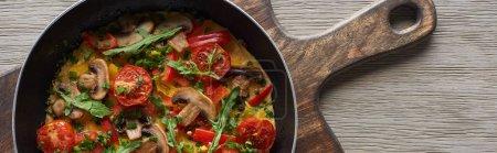 vista superior de tortilla casera con verduras y verduras para el desayuno en sartén sobre tabla de madera