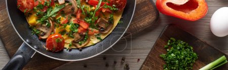 Photo for Top view of delicious homemade omelet in frying pan with ingredients on table - Royalty Free Image