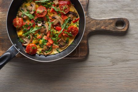 Photo for Top view of homemade omelet in frying pan on wooden board - Royalty Free Image