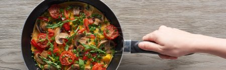 cropped view of woman cooking omelet with mushrooms, tomatoes and greens on frying pan