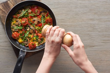 Photo for Top view of woman sprinkling pepper on omelet on frying pan - Royalty Free Image