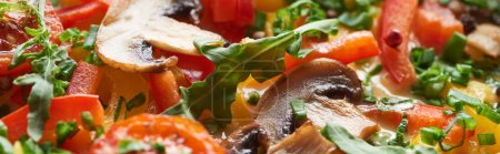 close up of homemade omelet with mushrooms, tomatoes and greens