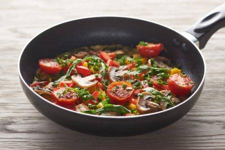 leckeres hausgemachtes Omelett mit Gemüse und Gemüse in der Pfanne auf dem Holztisch